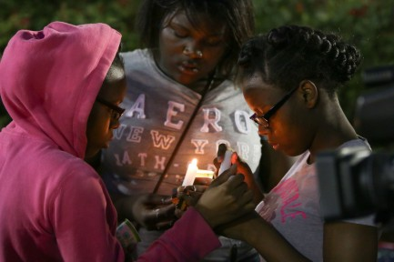 Two young girls light candles at a vigil for Walter Scott.